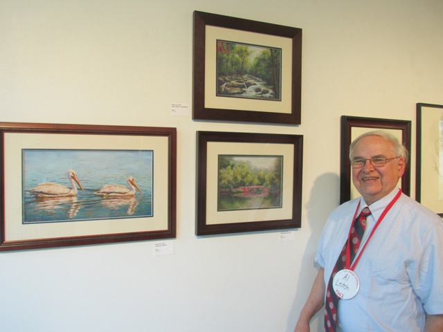 Al Leitch with his paintings.
