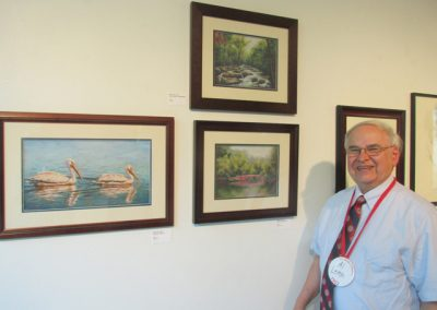 Al Leitch with his paintings